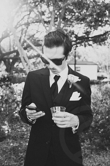 man wearing black suit holding drinking glass and black mobile phone photo