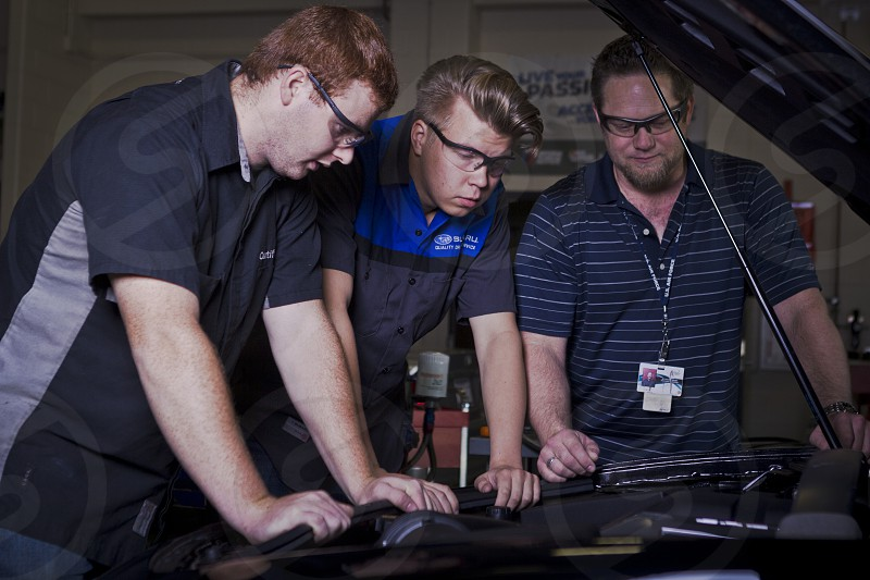 Three young men lean over a carhood.  photo