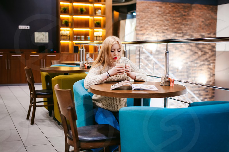 Picture of young lady sitting in cafe while reading magazine And drinks coffee photo