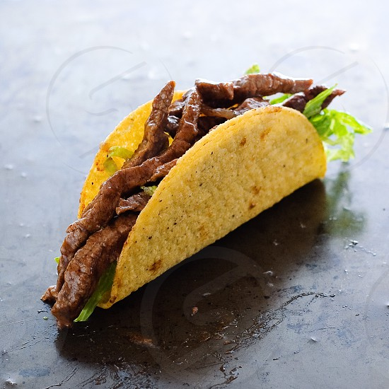 Beef taco on textured metal tray photo