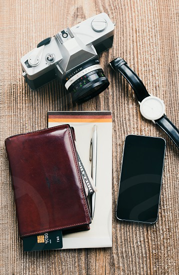 Smartphone with blank screen camera wallet dollar banknotes debit credit cards and notebook on wooden table. View from above. Portrait orientation photo