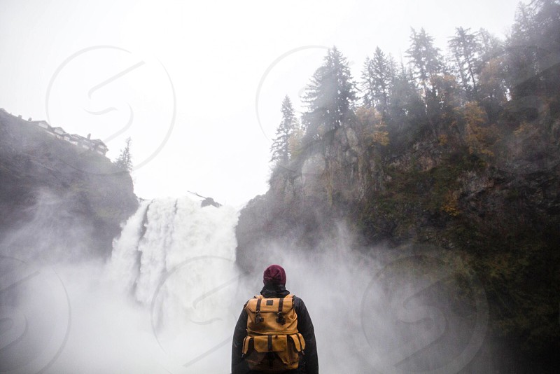 person wearing black jacket and yellow mountain backpack on smokey waterfalls photo