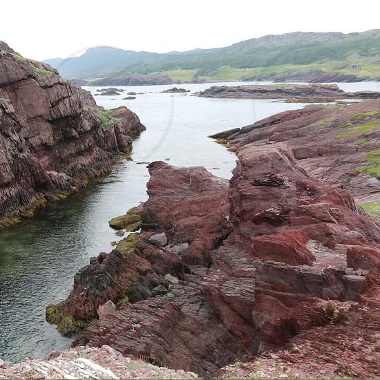 landscape photography of body of water near brown and maroon rocky mountain photo