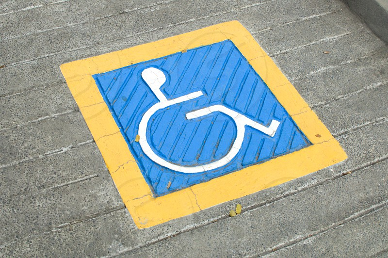 A yellow white and blue disabled signage on a road photo