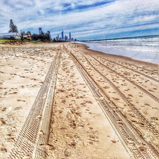 The road to Paradise - Surfers Paradise in the distance with tyre tracks in the sand. photo