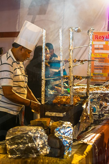 Indian street chef preparing and roasting chicken items. photo