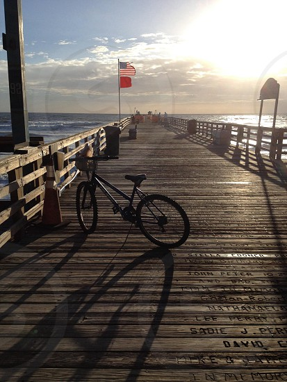 black bicycle on brown wooden sea dock photo