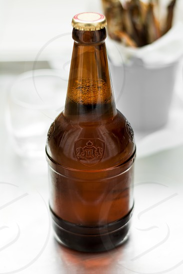 beer glassbottle capelin smoked white wooden background grey metalic selective focus photo