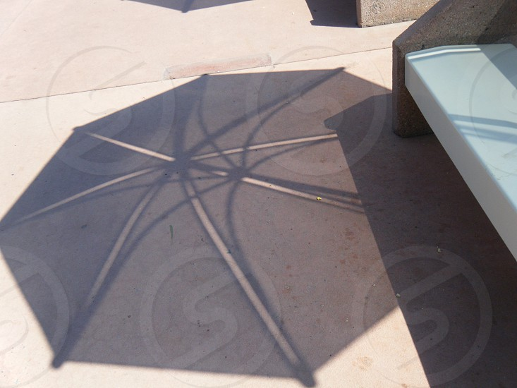 umbrella shadow mid-day evening concrete photo