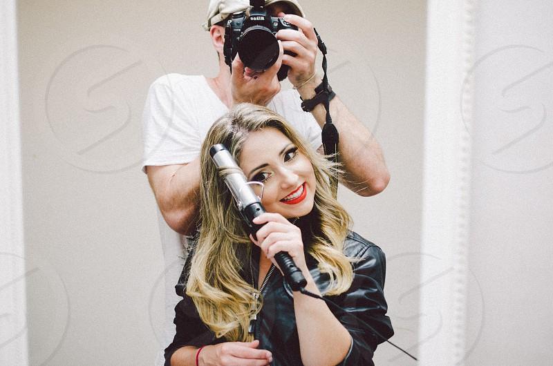 woman wearing black jacket curling hair with man behind taking photo photo