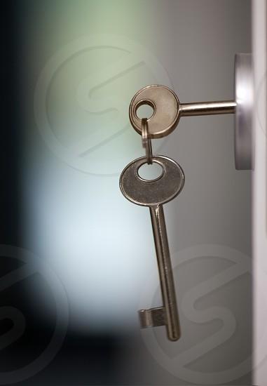 Close-up shot of keys in the keyhole. Locking or unlocking the door photo