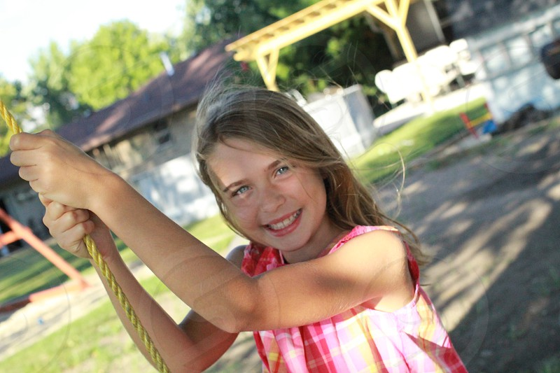 girl with pink sleeveless shirt holding yellow rope while smiling at daytime photo
