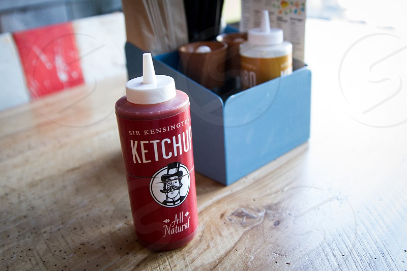 ketchup plastic bottle on brown wooden table beside condiments container photo