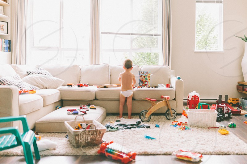 A little boy standing in a messy living room playing.  photo