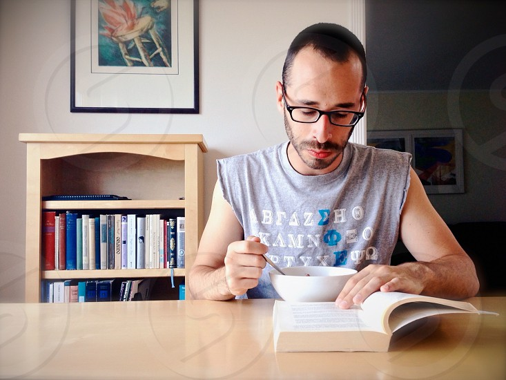 Man eating and reading a book photo
