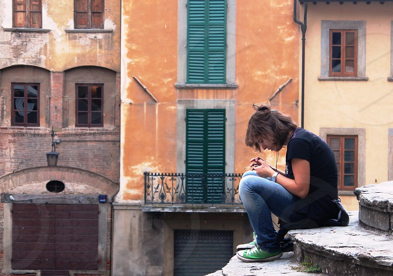 teenage girl listening to ipod on steps of church in  Tuscany photo