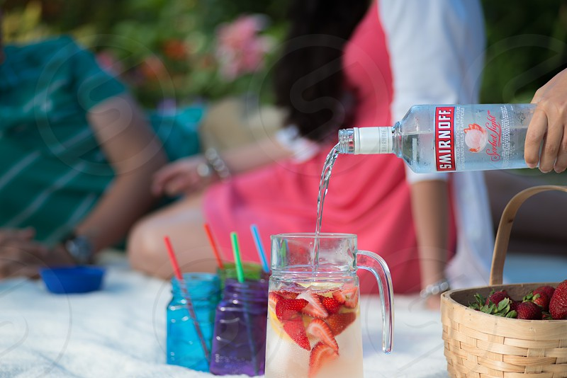 person pouring smirnoff in clear glass pitcher with sliced strawberries in tilt shift lens photo