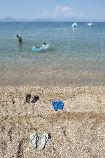 Slippers in the sand on the beach and people at sea.  photo