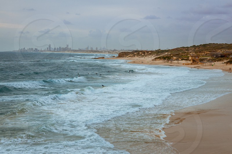 Surfers surf on the waves at Palmahim beach in Israel at sunset. photo