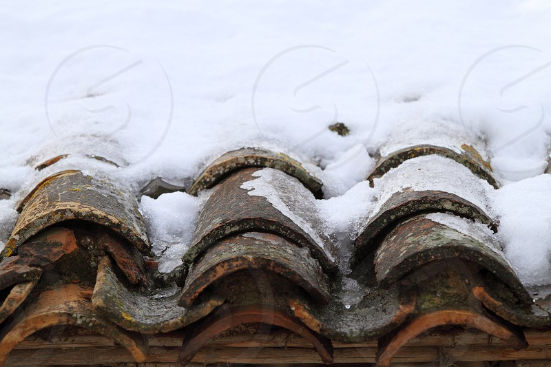 aged clay roof tiles snowed under snow architecture detail photo