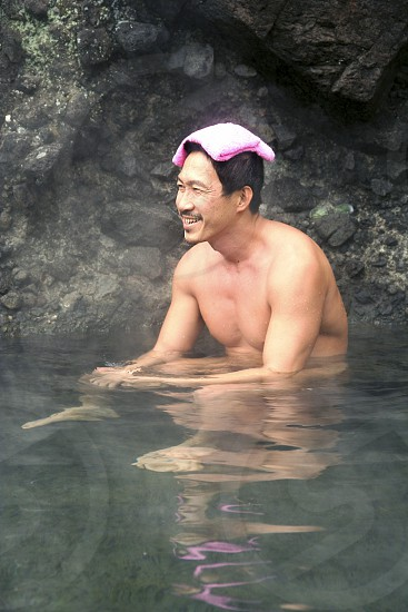 """A Japanese man relaxing at an open air hot spring called a """"rotemburo"""" in Japan.  Bathing in a natural atmosphere among the trees and under open skies is a favorite with Japanese.  Nowadays it is almost a requirement for any hot spring resort to have outdoor baths thanks to their popularity. photo"""