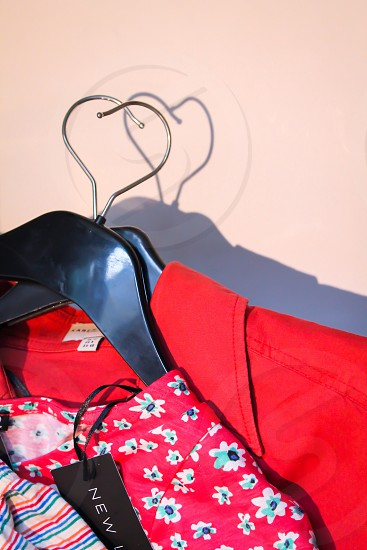 red cloth hanged on black cloth hanger photo