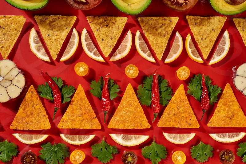 Creative geometric food pattern from mexican nachos corn chips fresh vegetables fruits greens chili garlic - ingredients for tomato chili sauce on a red background. Flat lay photo
