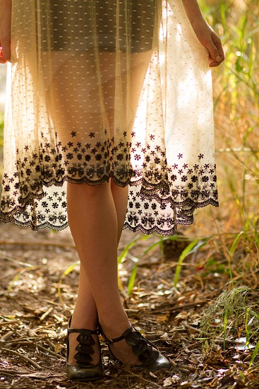 A young woman stands with her legs crossed in a backlit spotted laced dress photo