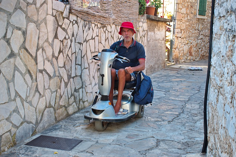 Portrait of senior man in electric wheelchair driving through the narrow streets of Primosten in Croatia photo