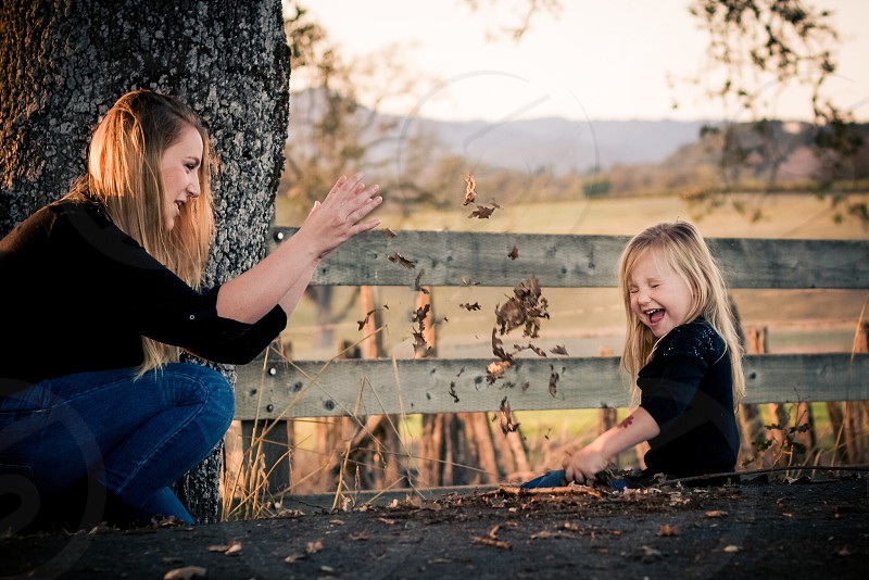 Mother and daughter fall leaves playing outdoors  photo