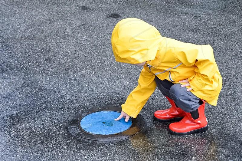 child in yellow rain coat pointing blue round manhole cover photo