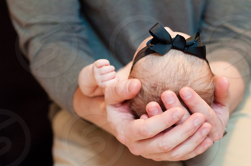 Father's hands holding newborn baby girl photo