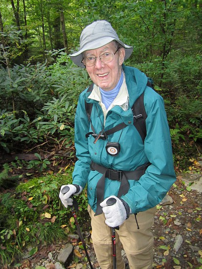 Older elderly happy gentleman all geared up and on a mountain hike. photo