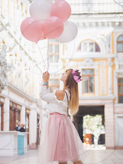 Portrait of young happy woman with paper crown colourful white and pink balloons smiling spinning around in city. Birthday girl enjoys her b-day and presents. photo