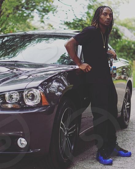 man in black t-shirt besides black car during daytime photo