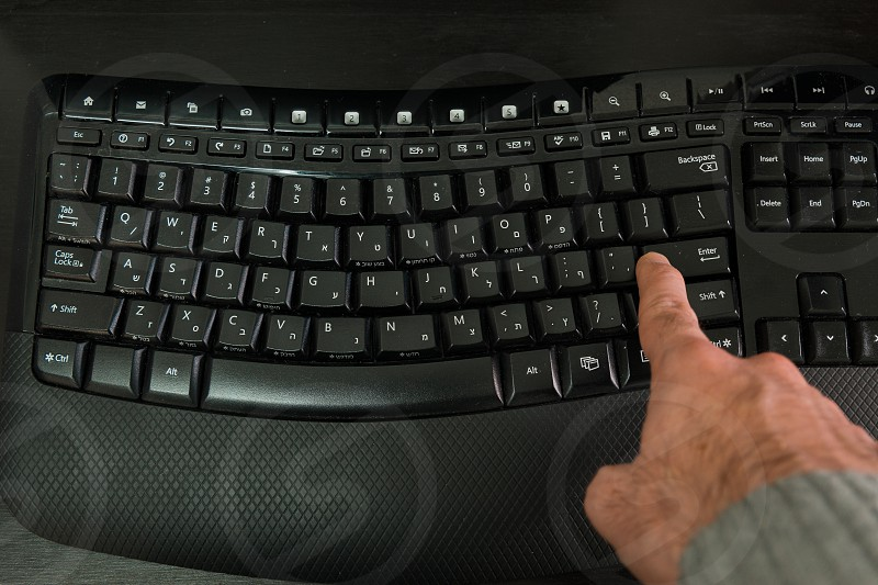 Man typing on a Wireless keyboard with letters in Hebrew and English - Press the Enter key - Top View photo