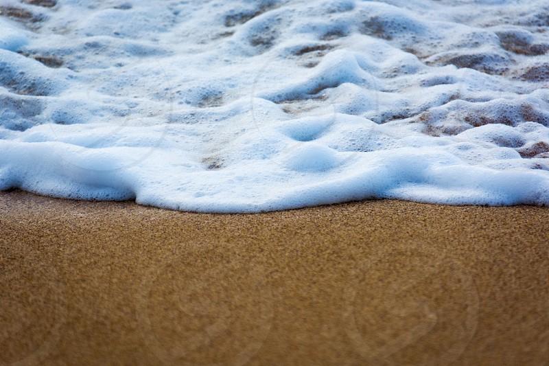 water beach sand closeup white foam dry blue brown photo