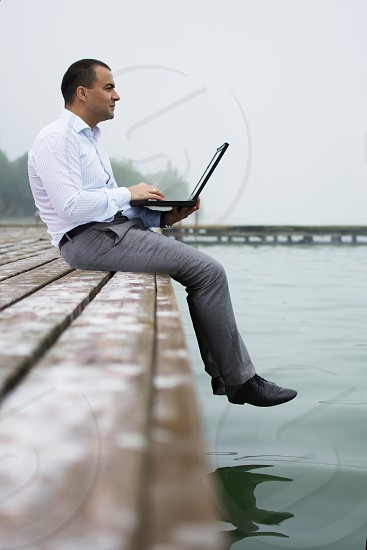 Young man in shirt and trousers with his laptop on a lake dock smiling and looking over the horizon. Foggy morning time about 6 a.m photo