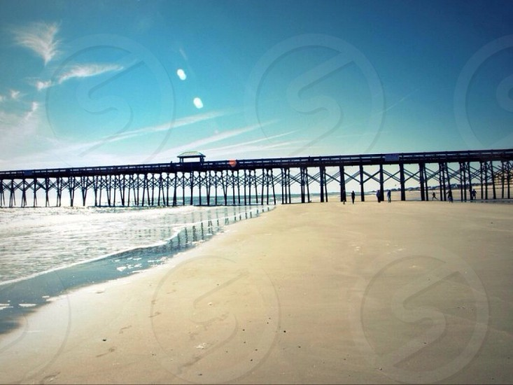 brown pier on top of ocean and brown sand beach under blue sky photo
