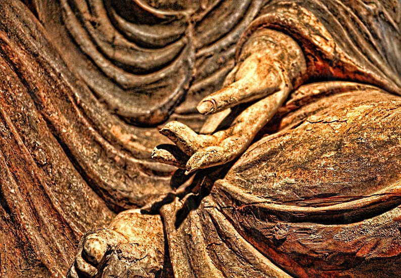 Abstract detail of the robes and hand of a Buddha statue photo
