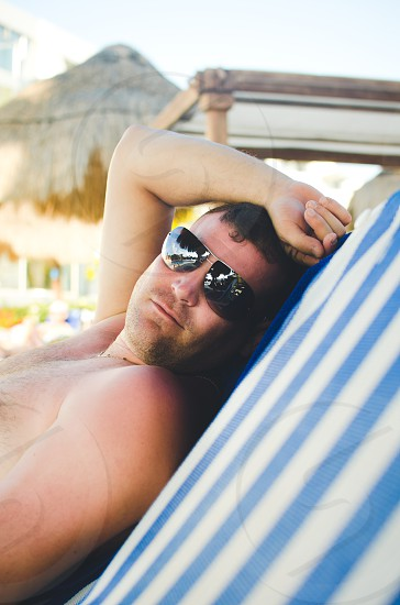 Man wearing sunglasses in the summer lying down on a lounge chair.  photo