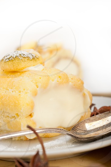 fresh homemade cream roll cake dessert and spices over white rustic wood table photo