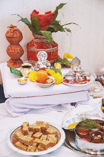 The Ganesha statue (Hindu god of wisdom) with red velvet of kalash on the back and worship items for thread ceremony (puja pooja) of indian wedding event photo