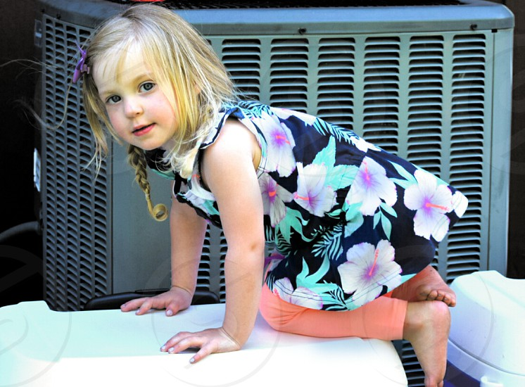 little girl crawling on cooler photo