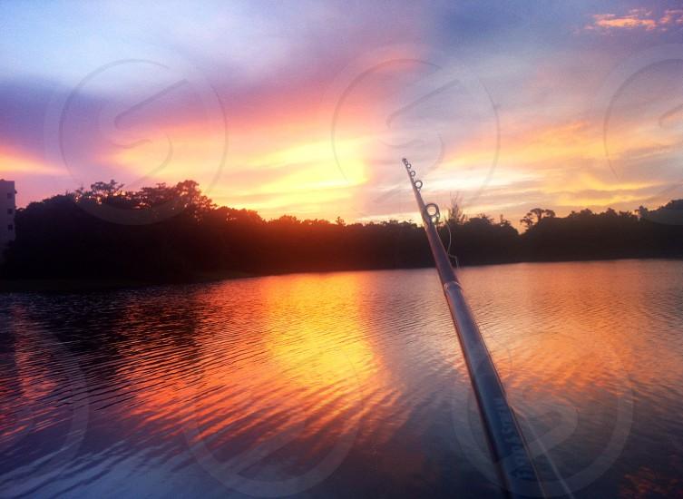 fishing sunset lake florida fishing pole trees photo