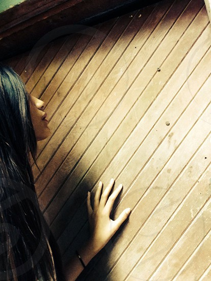 woman holding wooden wall photo