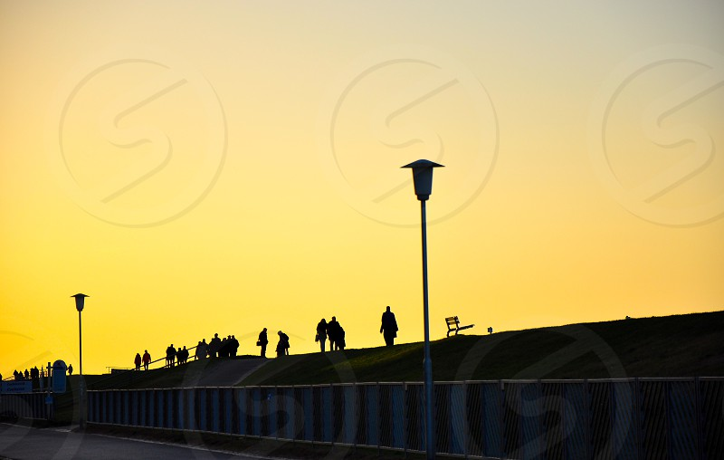 silouette of people walking on the promenade in cuxhaven at sunset Germany photo