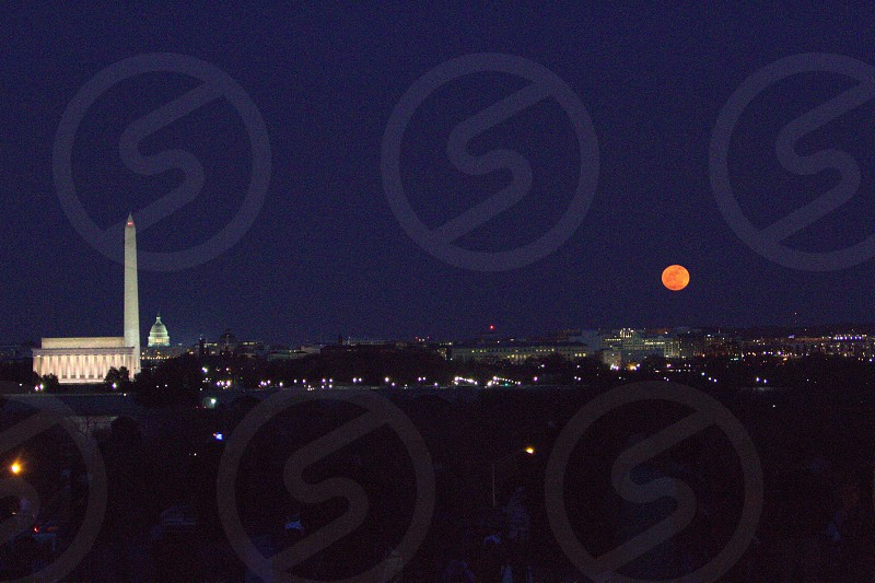 orange full moon in dark blue night sky over cityscape and lincoln memorial and obelisk photo