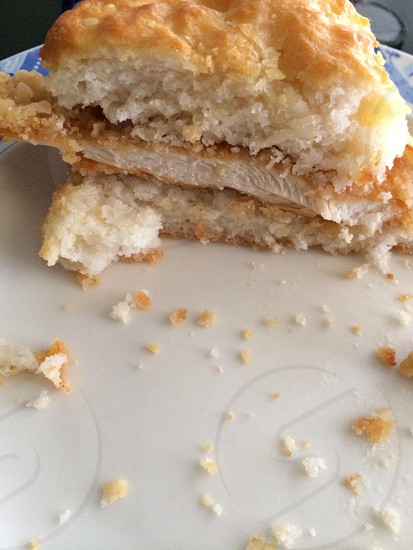 Chicken biscuit sandwich (cut in half with crumbs ) photo