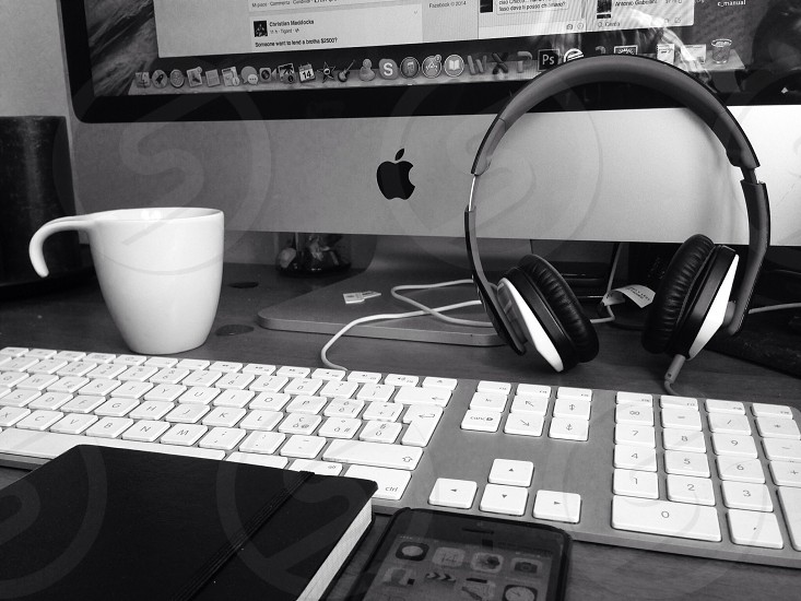 black and white headphones leaning against desktop apple computer with white ceramic mug and black notebook photo